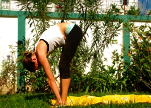 Exhale as you float down to the floor. Bend your knees in order to place your hands on either side of your feet.